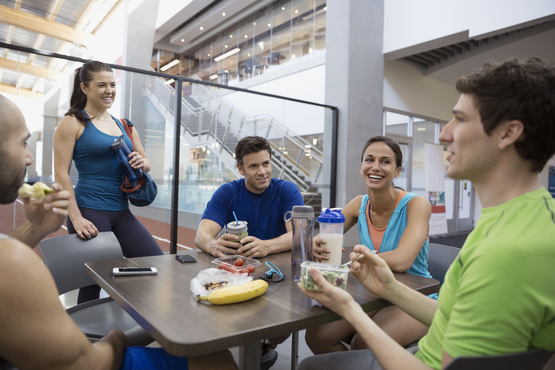 Amigos hablando y almorzando en el gimnasio
