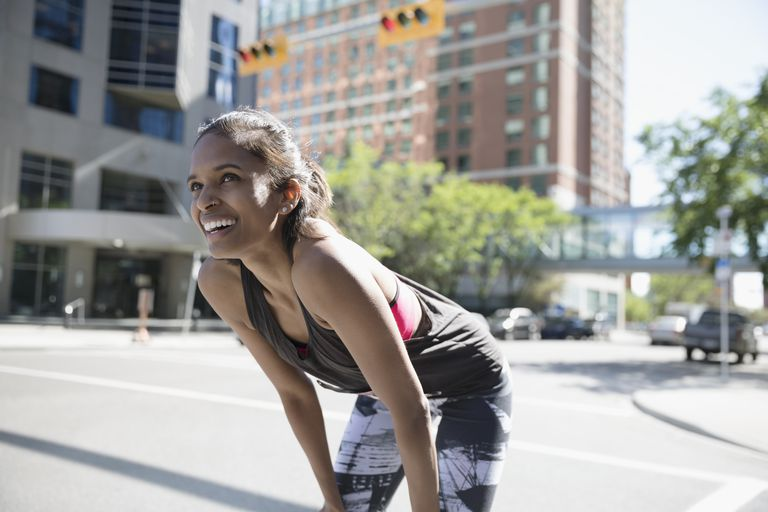 Smiling female runner resting with hands on knees on sunny urban street