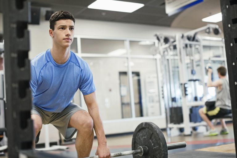 teenage boy lifting weights