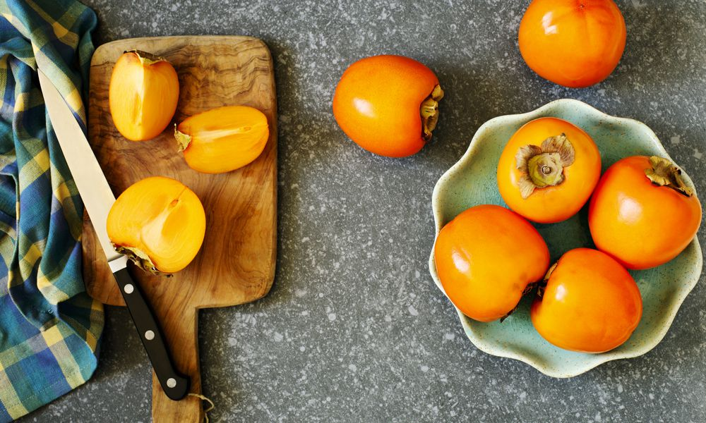 Delicious fresh persimmon fruits on table