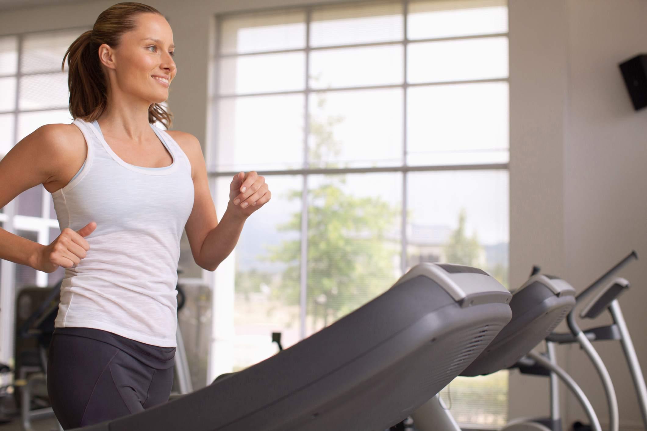Mujer con equipo de cinta de correr en casa