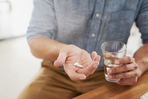 Man taking white supplement pills with water