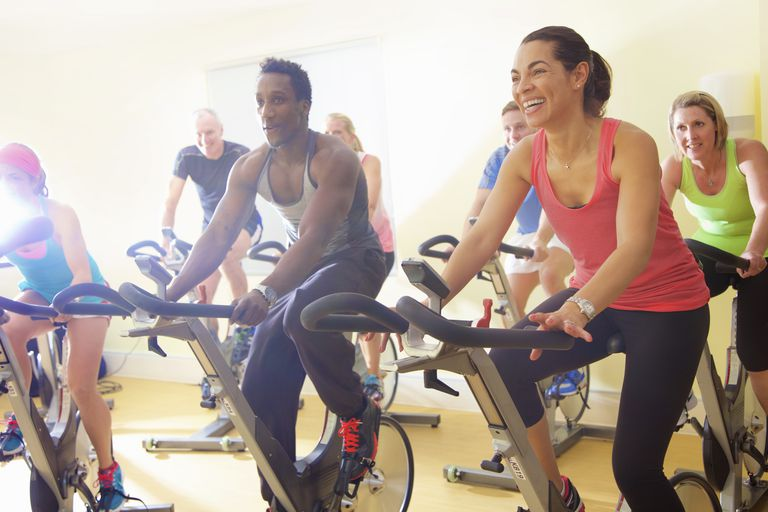 men and women in spin class