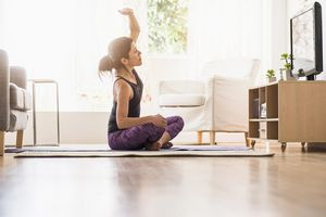 Side-view of woman exercising in living room