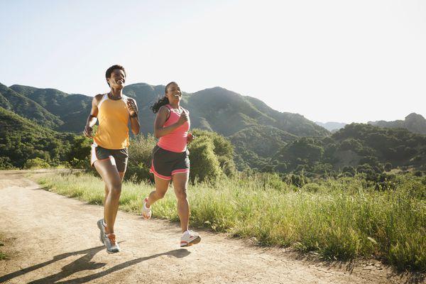 Two women running on an open grassland trail.