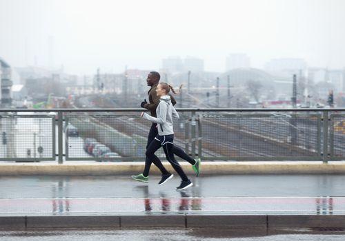Dos amigos corriendo por el puente urbano de la calle