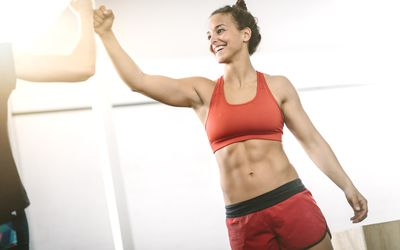 Woman in gym giving high five