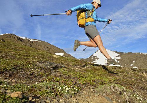 Mujer excursionista saltando cuesta abajo