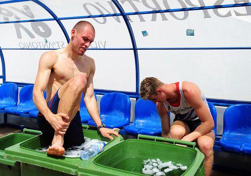 Los hurdlers Dai Greene (l) y Jack Green toman un baño de hielo después de su sesión de entrenamiento durante el campamento de preparación del Equipo GB de atletismo en el estadio Monte Gordo el 25 de julio de 2012 en Monte Gordo, Portugal.