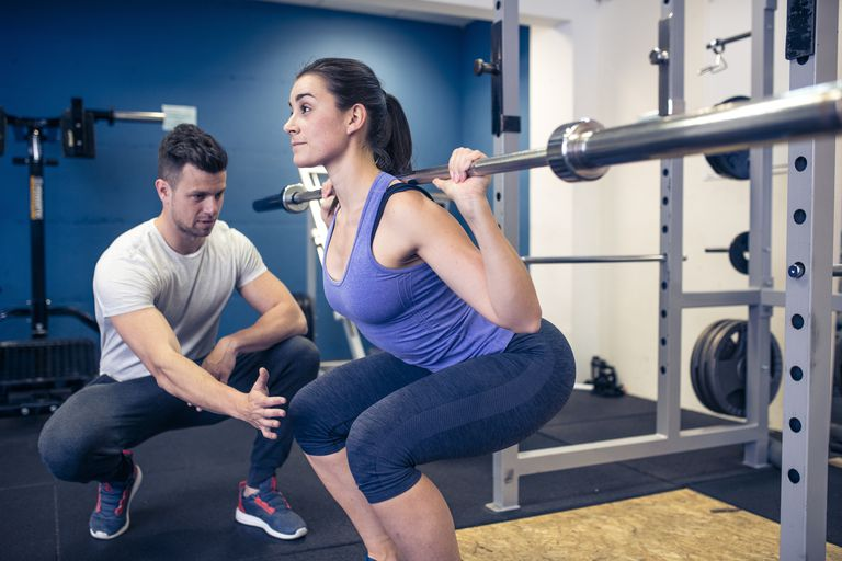Woman with personal trainer working out in a gym. Coach is advising her  what are 825e34c68865