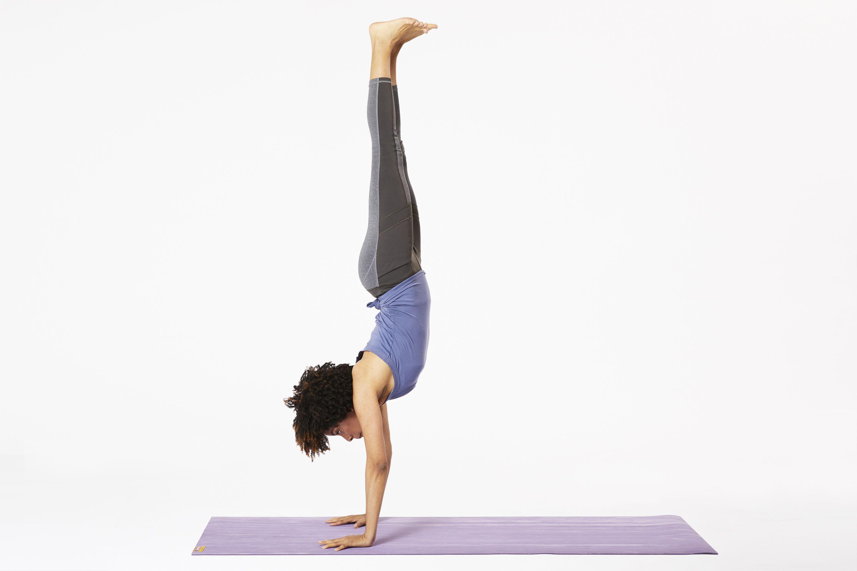 Woman on yoga mat doing handstand