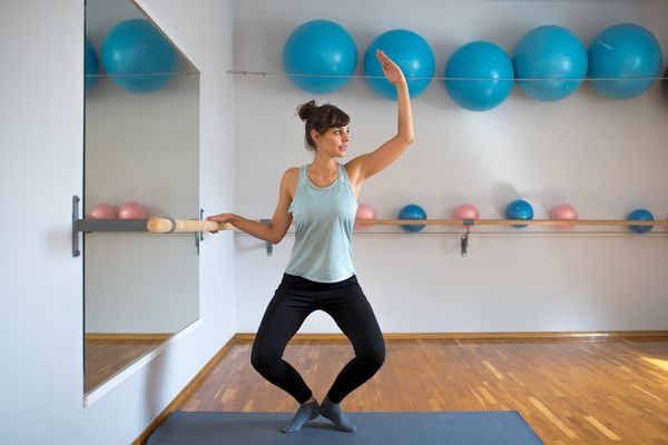Side view photo of a woman practicing with a barre in the studio