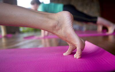 Feet of woman doing a plank on a yoga mat
