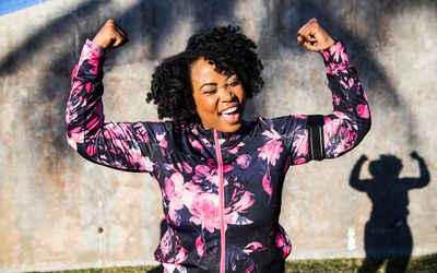 Woman smiling and flexing after overcoming her weight loss barriers