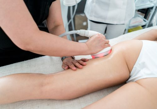 Woman getting an anti-cellulite lase treatment at the spa