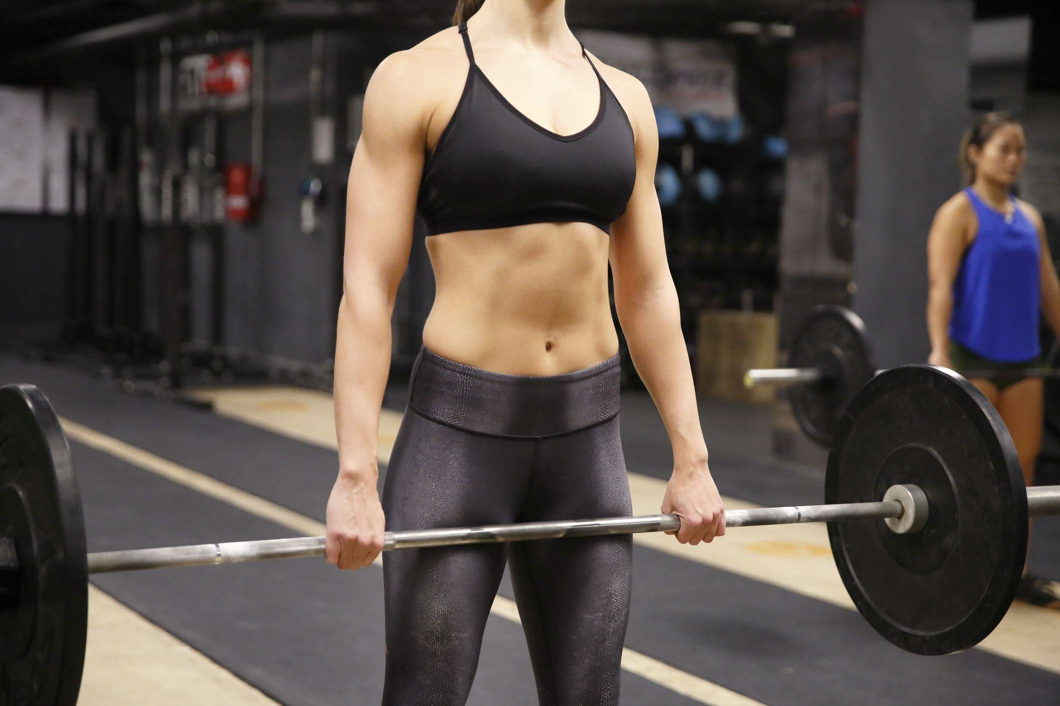 Woman holding barbell to do hang clean