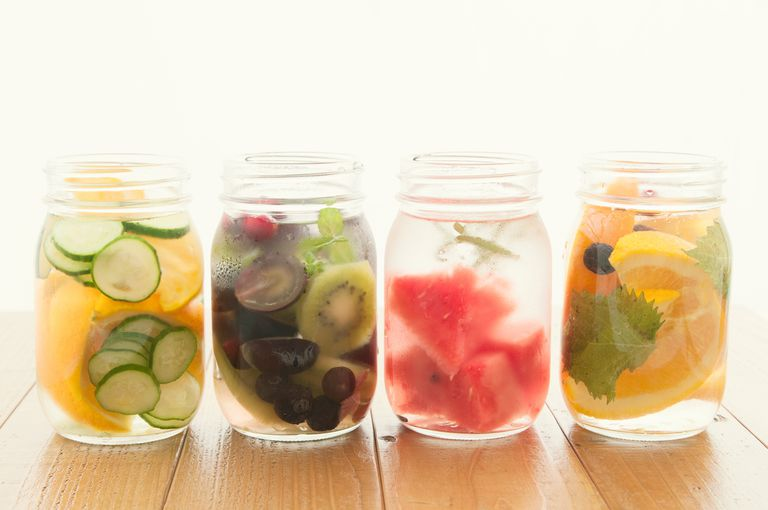 4 mason jars of water with fruit in them