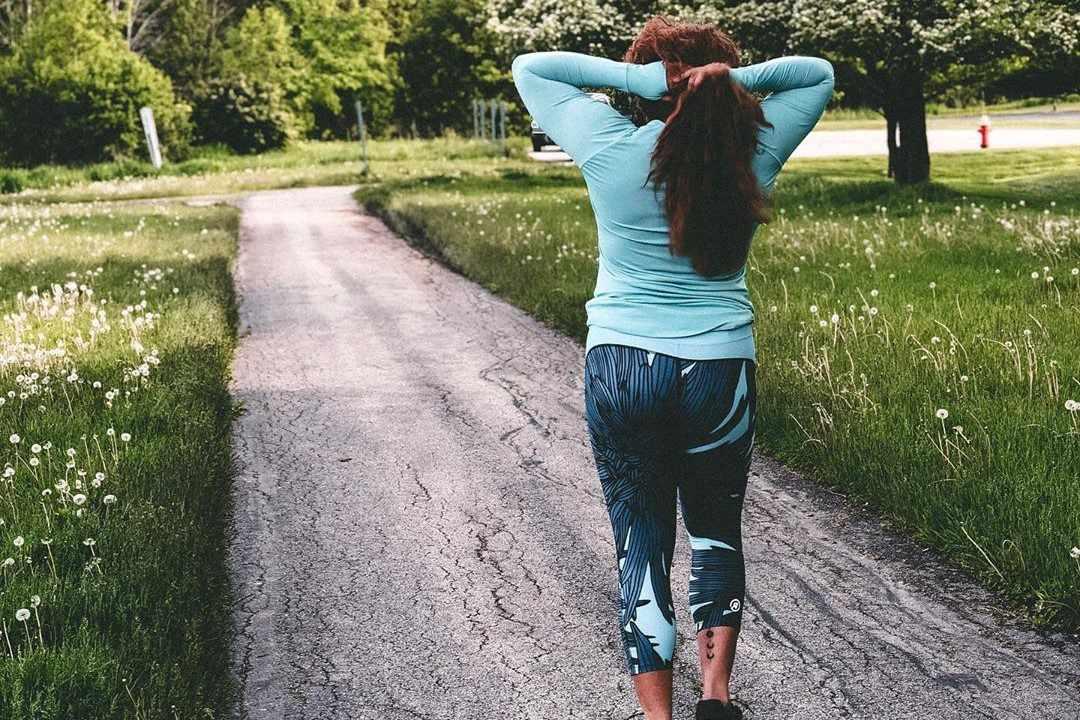 Una mujer en ropa deportiva Rsport a lo largo de un sendero pavimentado