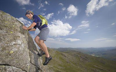 Hiker traversing rock outcrop