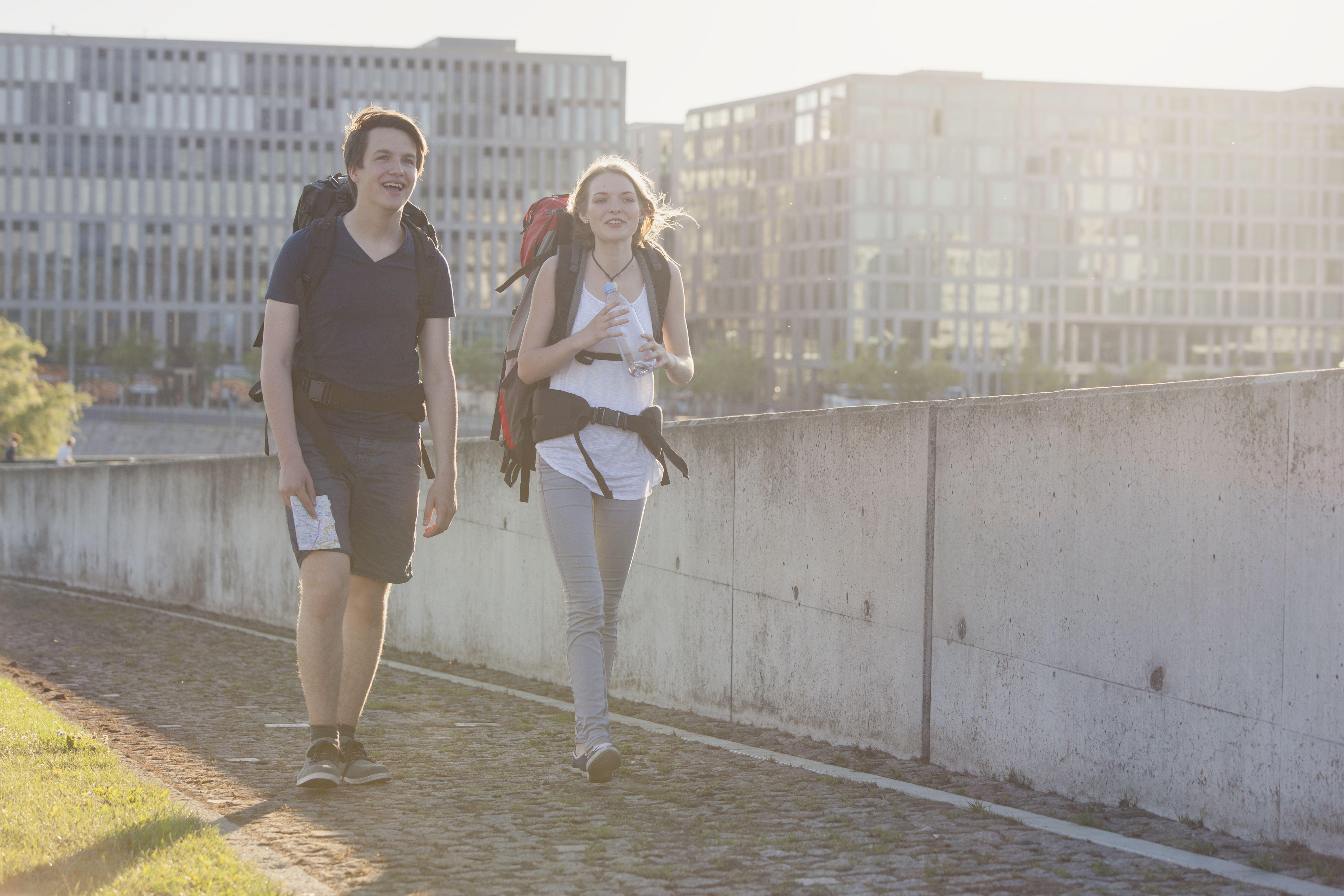 Young couple walking outside wearing backpacks