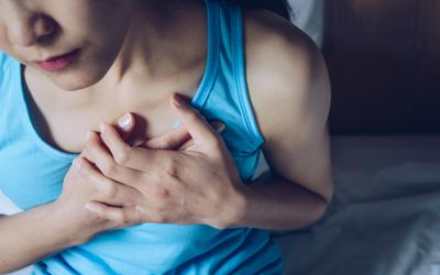 woman clutching her chest due to heartburn