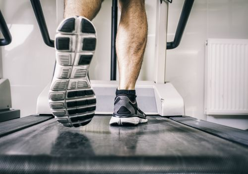 Man's feet walking on a treadmill