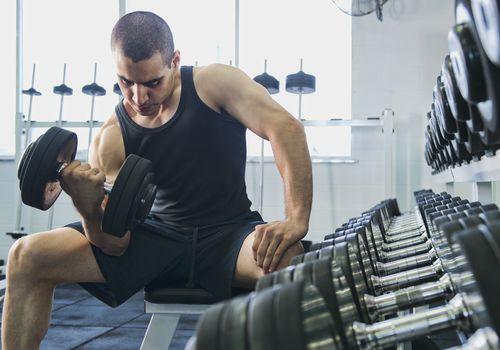 Un hombre haciendo flexiones de bíceps.