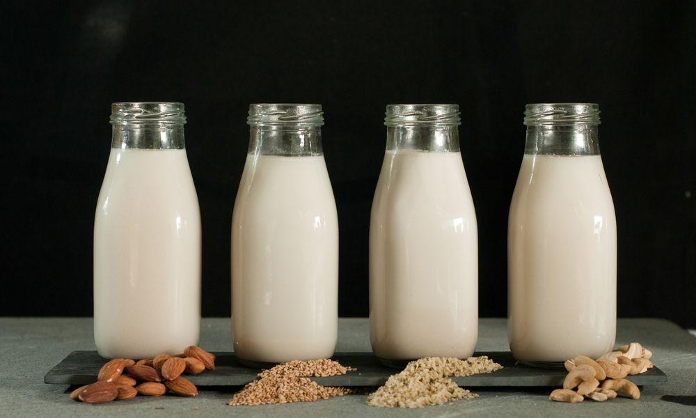 Various Types Of Milk Bottles Against Black Background - stock photo