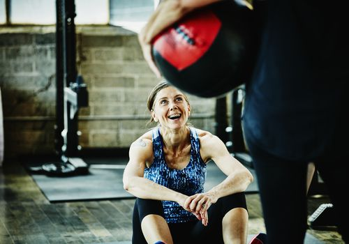 Laughing mature woman doing medicine ball crunches