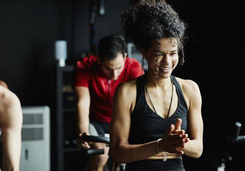 Mujer riendo durante la clase de ciclismo indoor en gimnasio