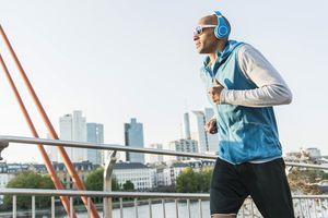 Germany, Frankfurt, man wearing headphones jogging on bridge