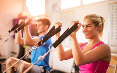 Smiling woman using the Megaformer pilates machine