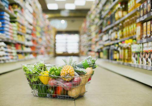Canasta de comestibles con frutas y verduras sentado en medio del pasillo de una tienda de comestibles