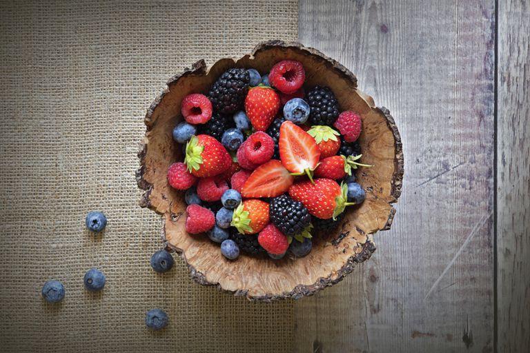 Wooden bowl full of raspberries, strawberries, and blueberries