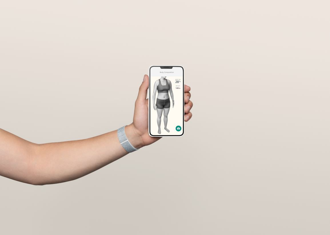 A person holding a smartphone showing a 3D body composition scan.