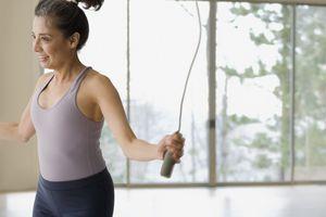 Hispanic woman jumping rope during workout
