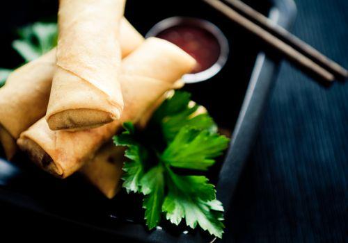 Foto de tres rollitos de primavera con salsa