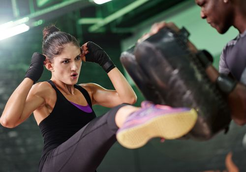 female mixed martial arts fighter kicking