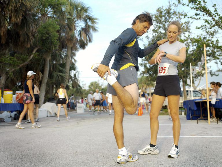 Man stretching next to a woman before a half marathon