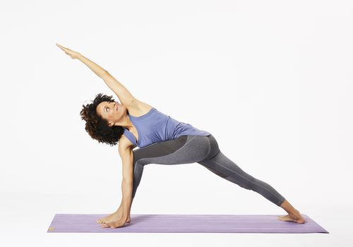 Woman doing revolved side angle pose on yoga mat