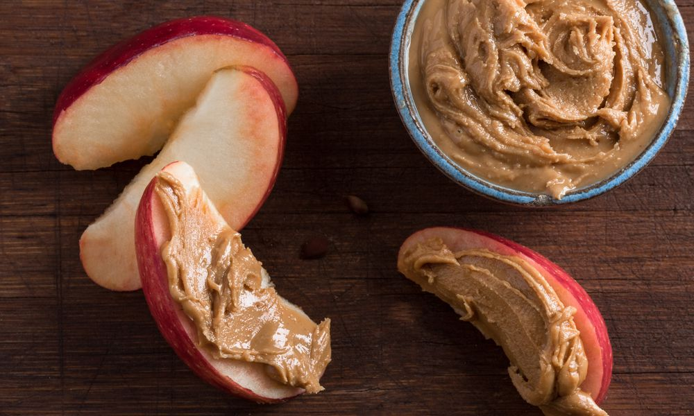 Close-Up Of Apple Slices With Peanut Butter On Table