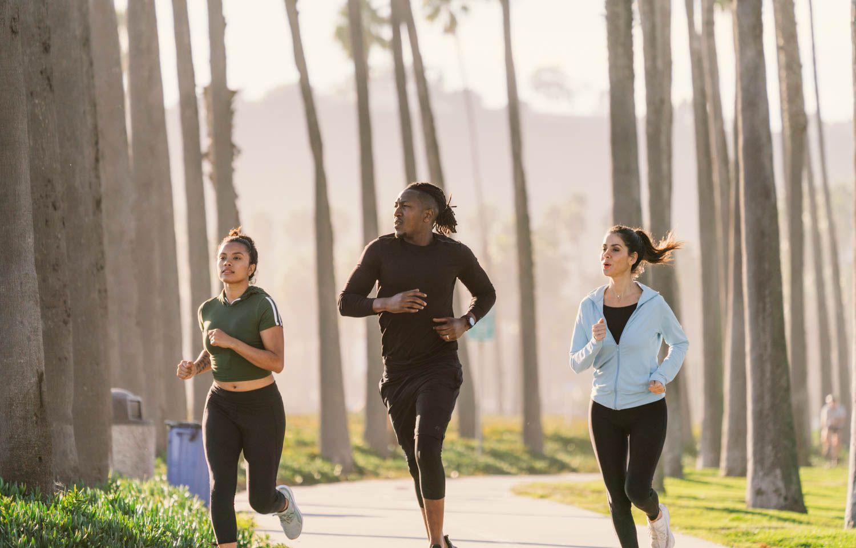 tres personas corriendo juntas en un parque