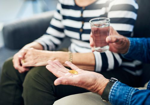 old person holding vitamins and a glass of water