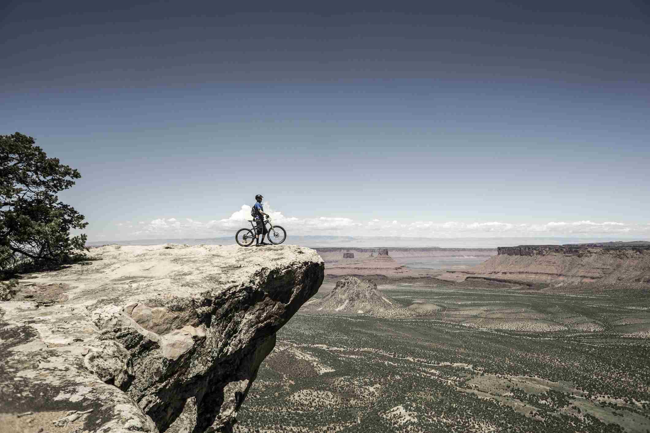 Hombre de pie junto a la bicicleta de montaña en el borde de un acantilado