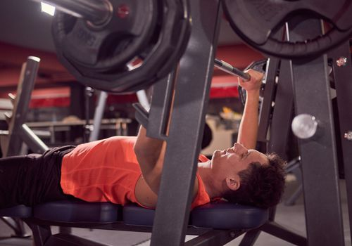 A man performing a bench press with a barbell and weights in a gym.