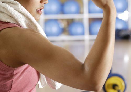 Mujer joven, doblar bíceps, en, gimnasio, primer plano, vista lateral