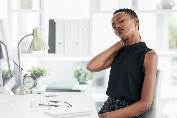 woman rubbing neck while sitting at desk