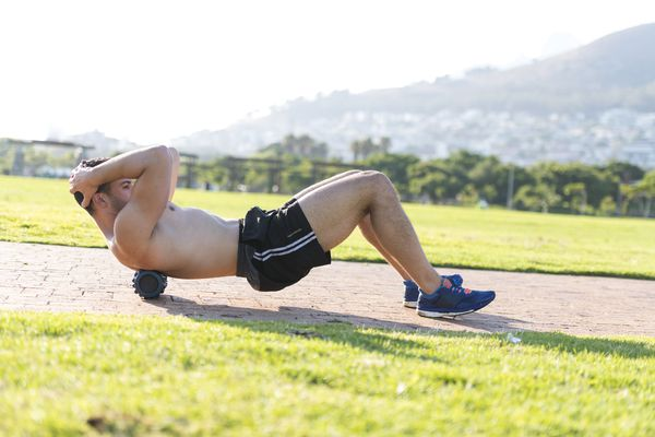 A young man performing exercises on a foam roller outdoors in a lush mountain area.