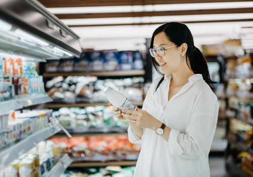 Young Asian woman grocery shopping in supermarket and holding a bottle of fresh milk - stock photo