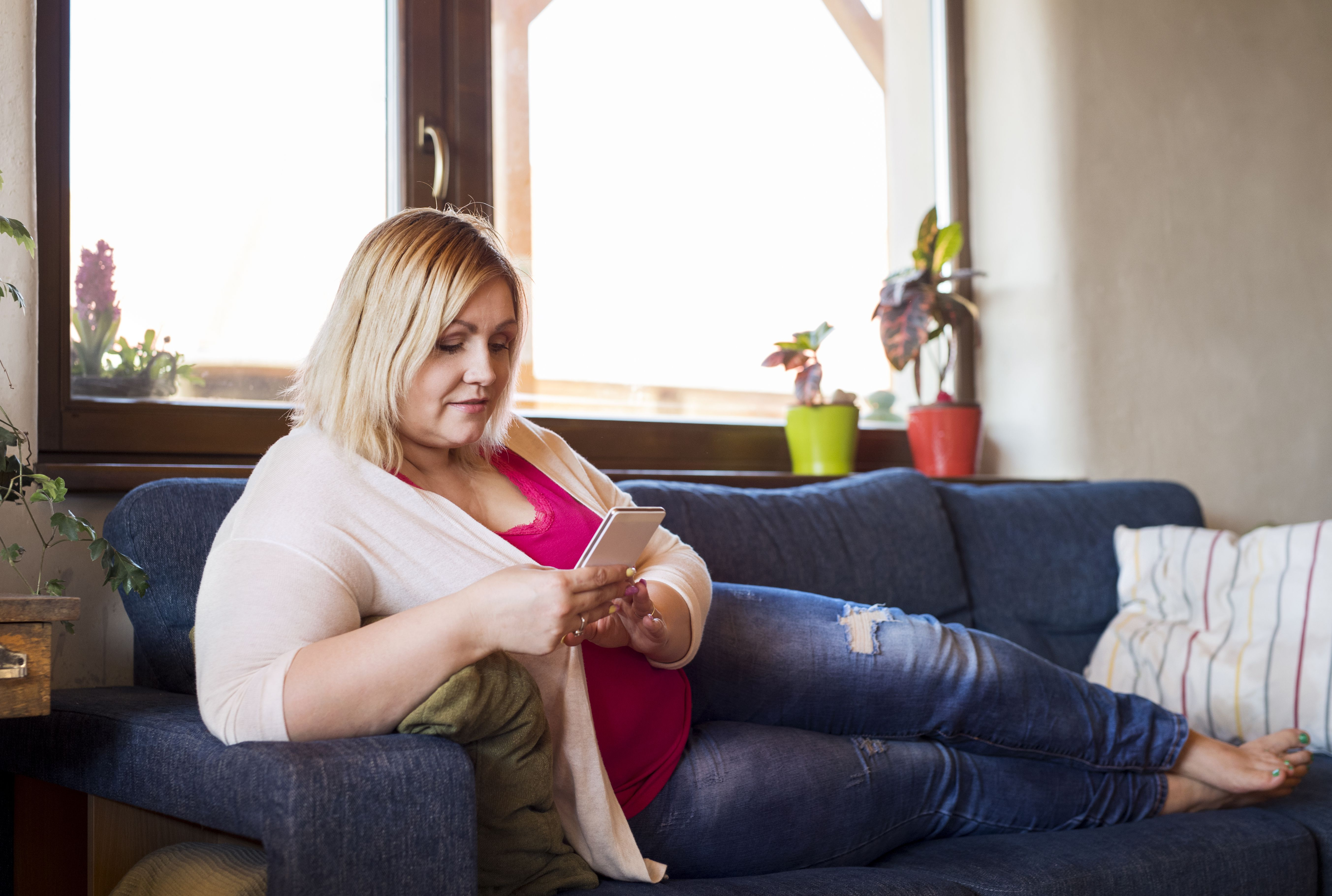 Attractive overweight woman at home lying on couch, holding smart phone, texting.